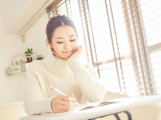 優しい笑みでノートに文字を書く女性