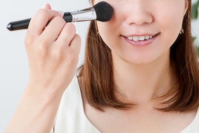 化粧ブラシでパウダーをのせる女性