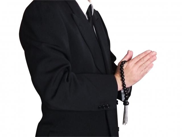 男性が喪服で数珠を手に合唱している姿