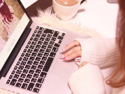 ノートパソコンのキーボードを打つ女性