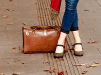 鞄と足を交差させて立っている女性の足元